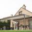 Ein helles Haus mit großem Garten und Terrasse. Die Terrasse wird von einer Markise beschattet. Die Markise ist an der Hauswand befestigt und steht vorne ähnlich, wie bei einem Terrassendach auf zwei Säulen.