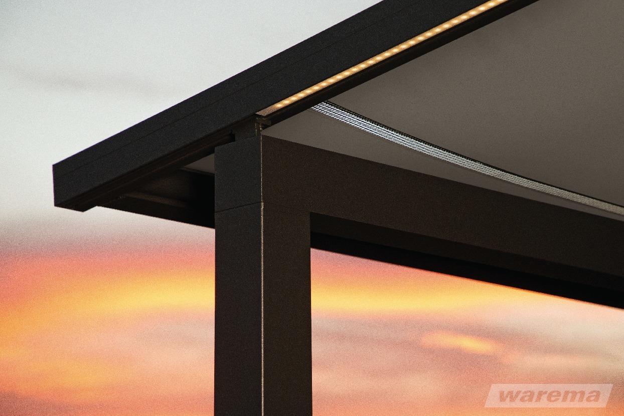 Die Pergola Markise Warema P60 mit integriertem Gitternetz. Im Hintergrund ein Sonnenuntergang.
