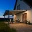 Weißes Haus mit Pergola Markise Warema P60 mit LED-Beleuchtung am Abend.